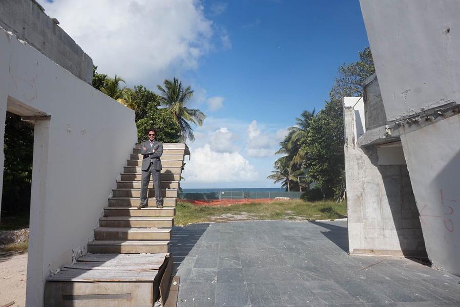 图为经纪人Alexander Goldstein站在卡洛斯·萨帕塔设计的房屋残余上