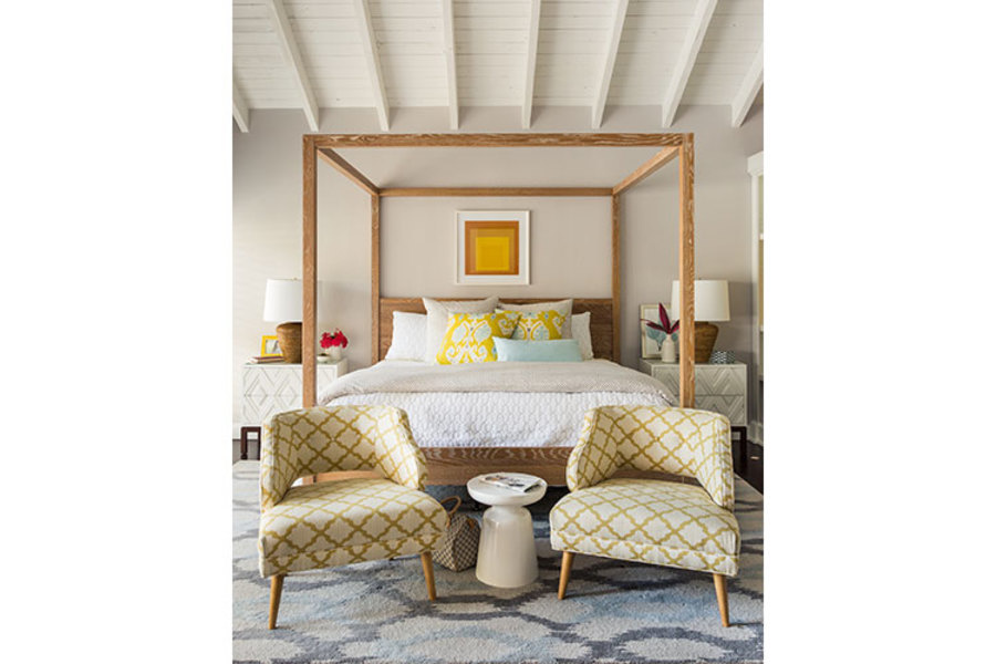 A beamed wood ceiling sets the tone for this pattern-rich modern-eclectic style bedroom designed by M