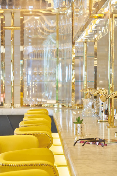 Elegant gold detailing and bright yellow leather stools give this bar the look of modern luxury.