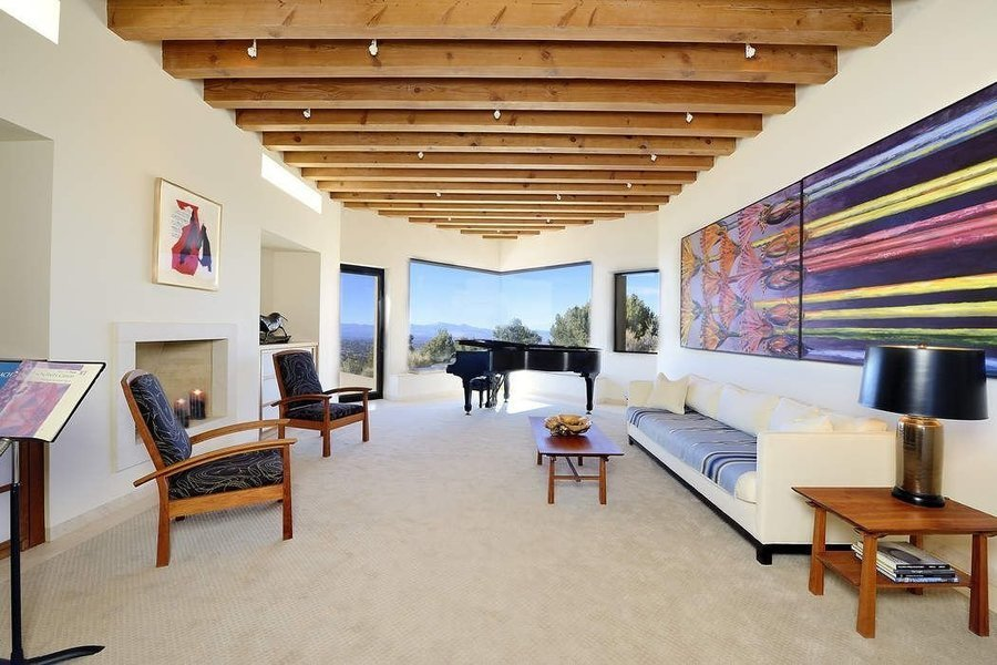 Perched high above Santa Fe in the Santa Fe Summit community, this stately three-bedroom, four-bathro